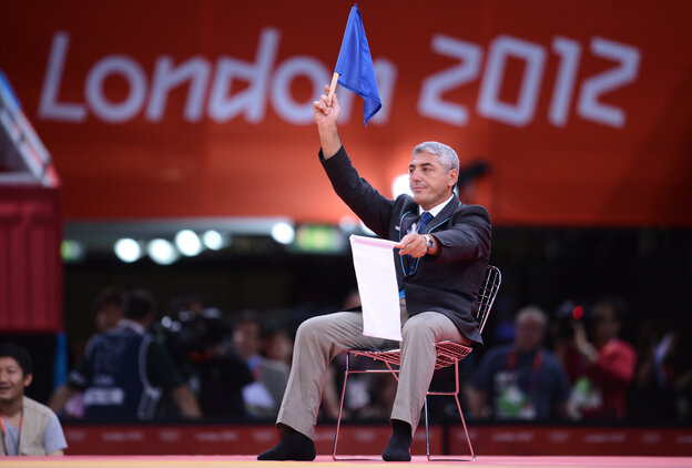 A judo judge waves a blue flag to award victory to South Korea's Cho Jun-Ho Sunday. But moments later, judges raised white flags instead, giving the win to Masashi Ebinuma of Japan.