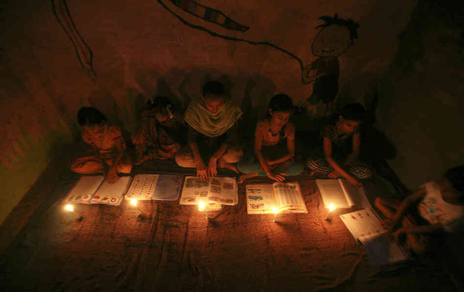 Muslim girls study by candlelight Monday inside a madrasa, or religious school, in Noida, on the outskirts of New Delhi. Three regional power grids collapsed, causing a massive power outage that blacked out more than half of India.
