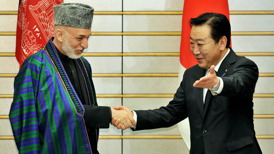 Afghan President Hamid Karzai is greeted by Japanese Prime Minister Yoshihiko Noda in Tokyo on July 9. The international community recently pledged $16 billion in additional aid, but wants Karzai to crack down on rampant corruption.