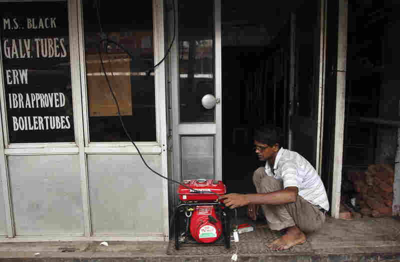 A shopkeeper fixes an electric generator at his shop in New Delhi.