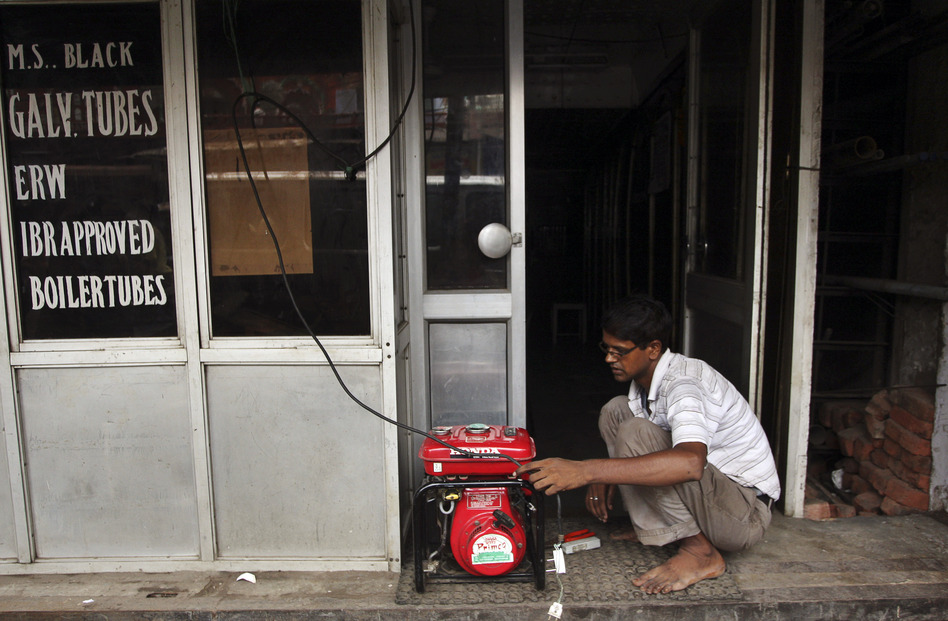 A shopkeeper fixes an electric generator at his shop in New Delhi. (AP)