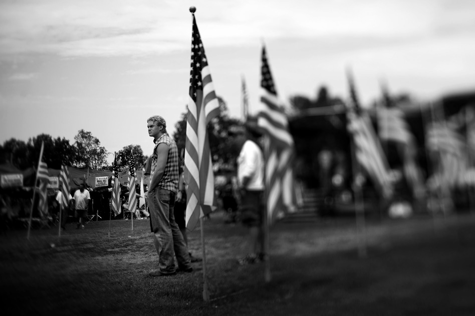 Veterans stand in the center of the grounds, surrounded by American flags. (NPR)