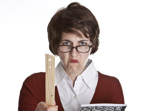 An angry teacher holding a composition book and pointing a ruler.