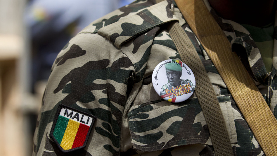 A soldier wears a button bearing the image of coup leader Capt. Amadou Haya Sanogo with the words 'President, CNRDRE,' the French acronym of the ruling junta, as he stands guard at junta headquarters in Kati, outside Bamako, Mali. (AP)