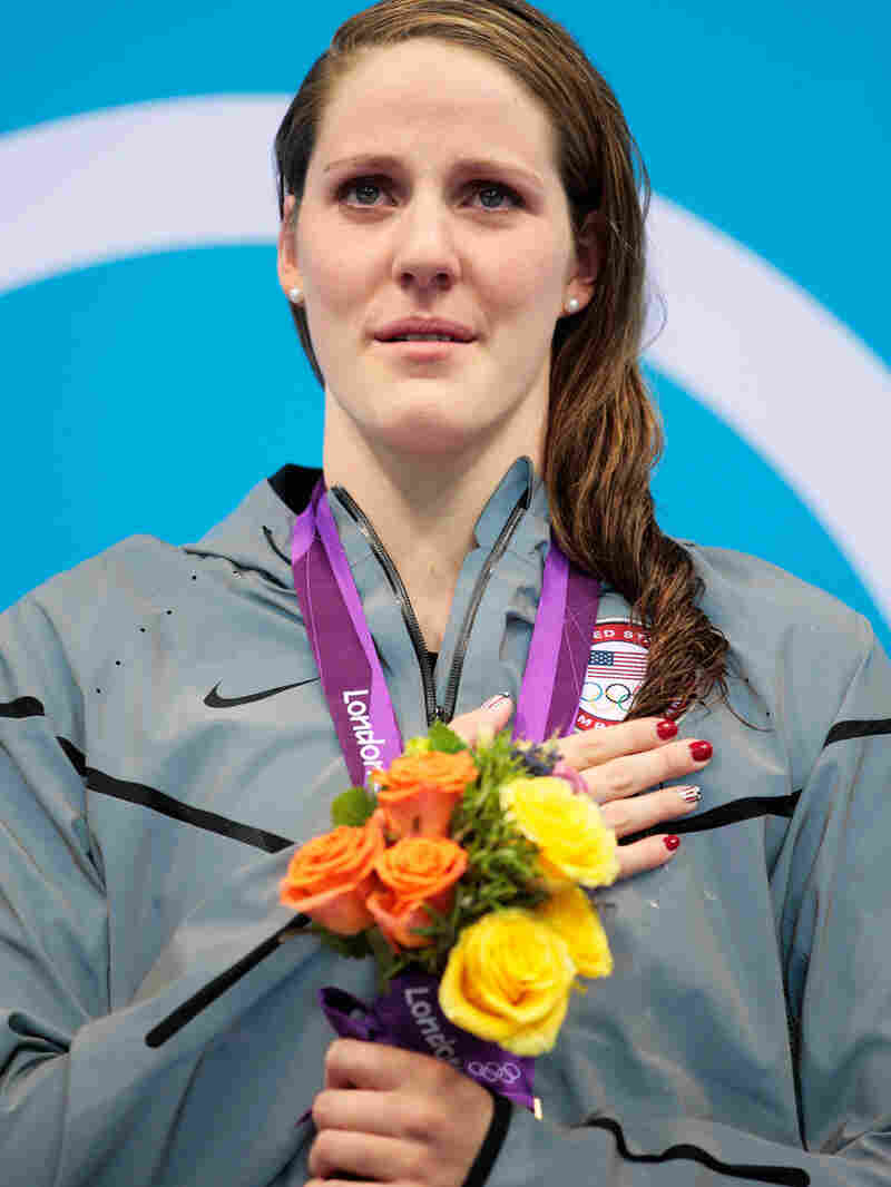 """Missy Franklin stands on the podium with her gold medal, after winning the 100m backstroke at the London 2012 Olympic Games. Of that moment, she says, """"I was trying to sing, but I was like, crying, at the same time."""""""