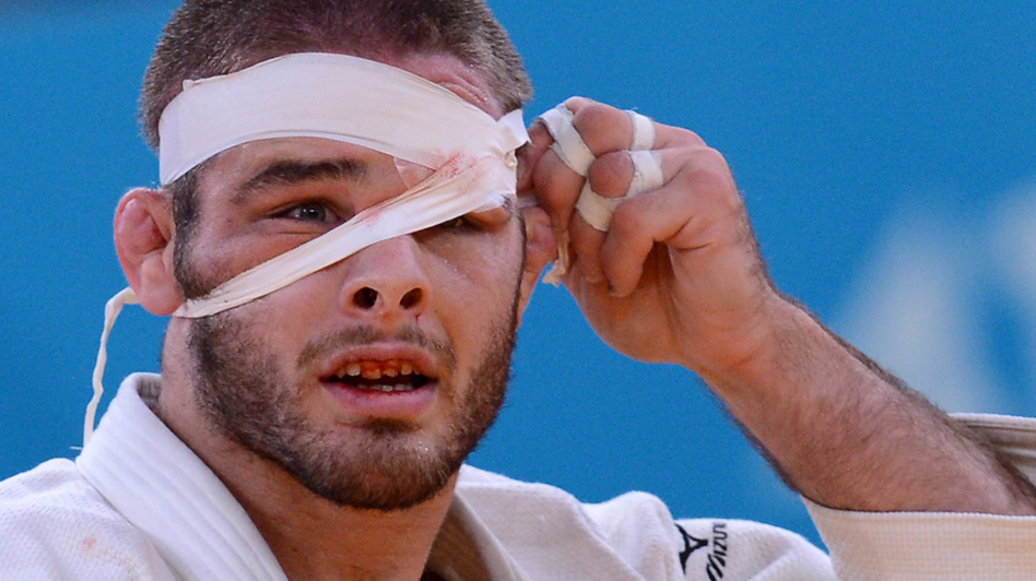 Travis Stevens adjusts his bandage as he competes with Germany's Ole Bischof during their men's -81kg judo contest semi-final match. (AFP/Getty Images)