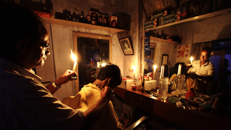 During the blackout on Tuesday, an Indian barber cut hair by candlelight in his shop in Kolkata. (AP)