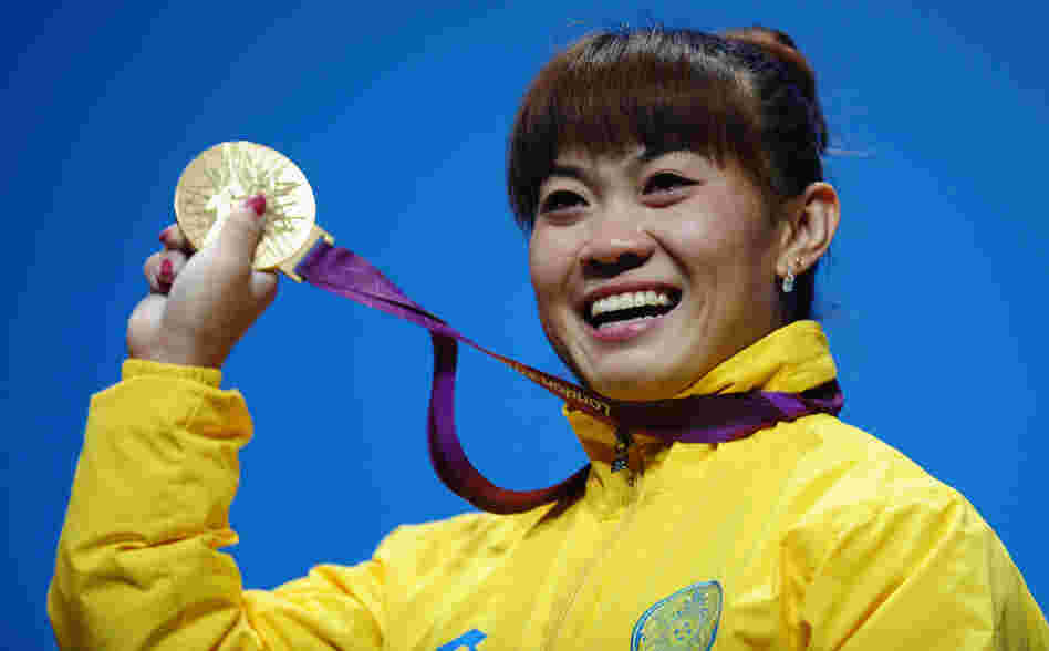 Plenty To Smile About: Weightlifter Maiya Maneza of Kazakhstan celebrates on the podium with her new 400-gram gold medal, matching the feat of her compatriot Zulfiya Chinshanlo. The Kazakh Olympians will each receive a $250,000 bonus.