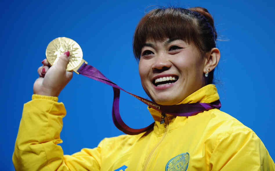 Plenty To Smile About: Weightlifter Maiya Maneza of Kazakhstan celebrates on the podium with