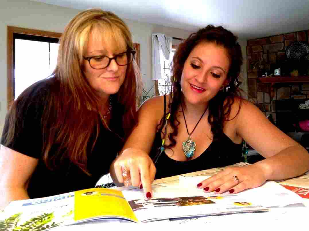 Emily Macri looks over a college brochure with her mother, Maureen O'Brien, in Kingman, Ariz. Macri is transferring to Northern Arizona University so that she can pay in-state tuition.