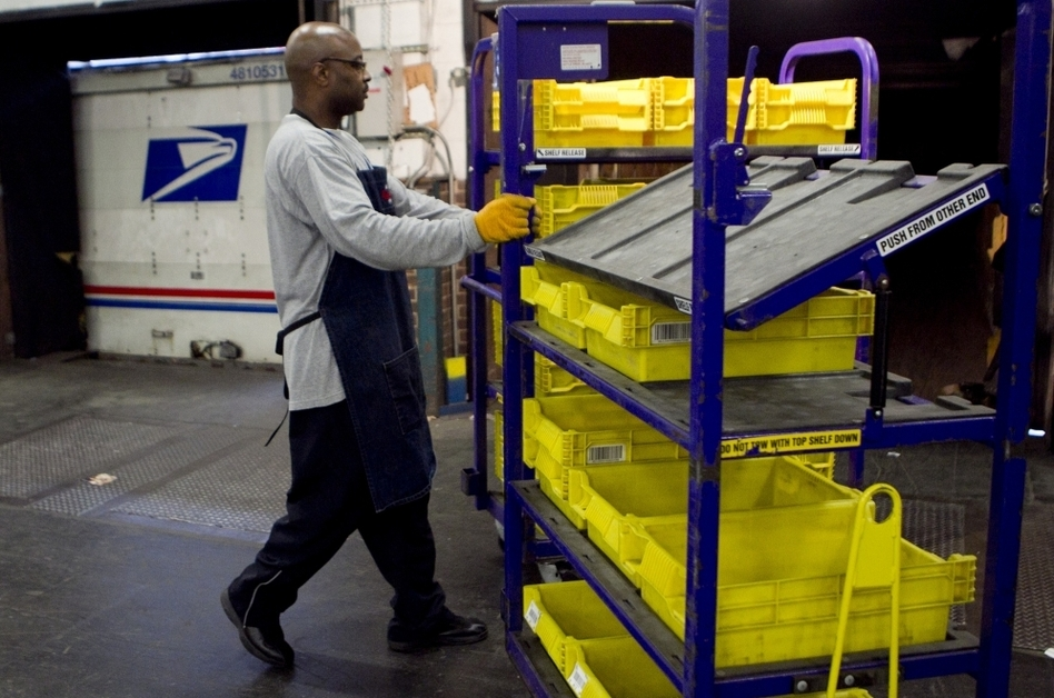 An employee loads flat trays onto a truck at the U.S. Postal Service processing and distribution center in Merrifield, Va.