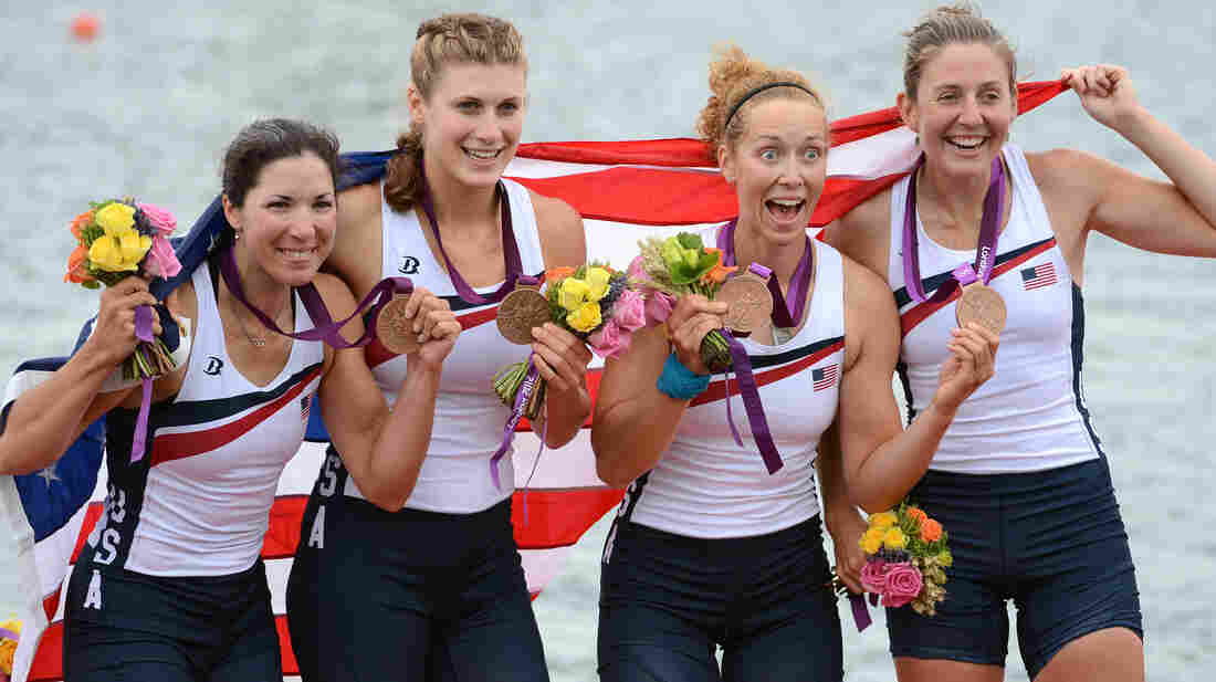 Adrienne Martelli, Megan Kalmoe, Kara Kohler and Natalie Dell of the United States celebrate on the podium after winning bronze in the women's quadruple sculls at Eton Dorney in Windsor, England.