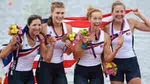 Adrienne Martelli, Megan Kalmoe, Kara Kohler and Natalie Dell of the United States celebrate on the podium after winning bronze in the women's quadruple sculls at Eton Dorney in Windsor, England.