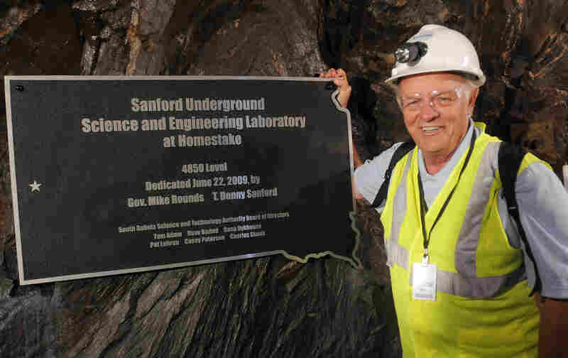 Businessman and philanthropist T. Denny Sanford has pledged $70 million to the Sanford Underground Science and Engineering Laboratory. He stands next to a plaque dedicating the 4,850 foot level, where several experiments will be set up, in 2009.