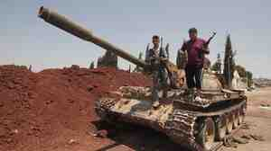 Anti-Assad fighters stood atop a captured army tank on Wednesday in the village of Anadan, about 4 miles northwest of Aleppo.
