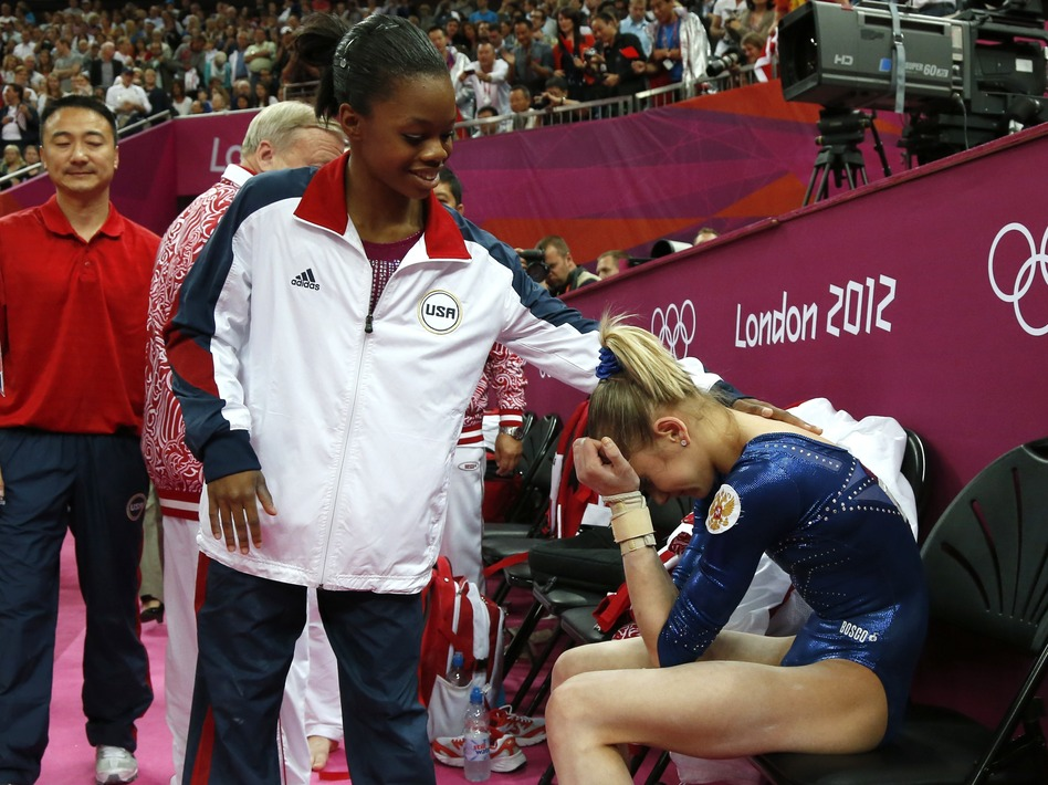 After Thursday's competition, American Gabby Douglas consoles silver medalist Victoria Komova of Russia. (AFP/Getty Images)