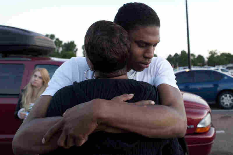 """Isaiah Bow hugs his mother, Shamecca Davis, after being questioned by police outside Gateway High School where he and other witnesses were brought after the shooting. After leaving the theater Bow went back in to find his girlfriend. """"I didn't want to leave her in there. But she's OK now,"""" Bow said."""