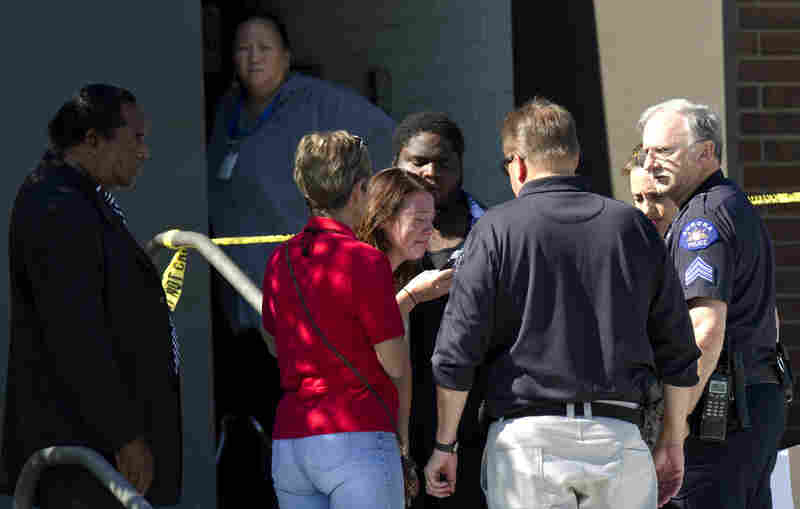 A woman is overcome with emotion while surrounded by counselors, police and clergy outside the high school.