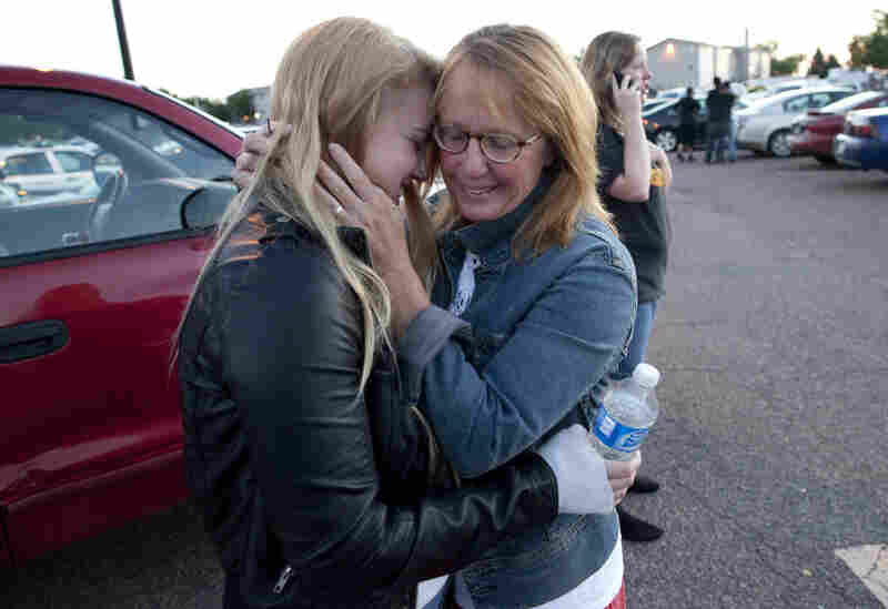 Emma Goos, 19, hugs her mother, Judy Goos, outside the high school. Emma was in the third row of the theater when the shooter entered. She helped apply pressure to an injured man's head.