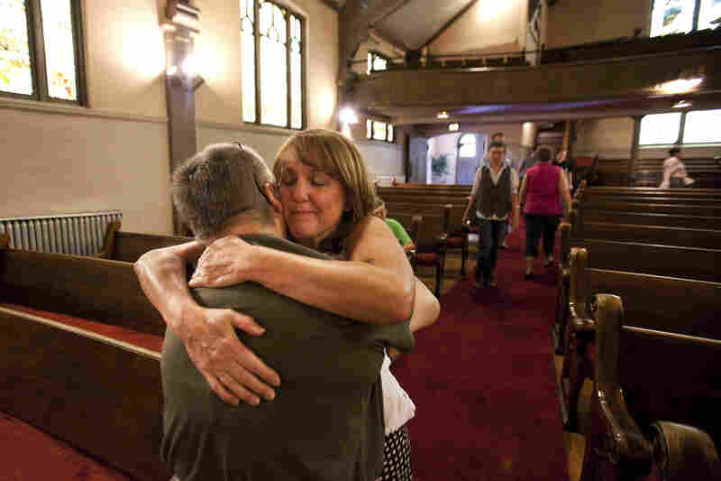 Gail Stevens (left) comforts Judy Goos at the Grant Avenue United Methodist Church in Aurora on July 22. Goos' daughter Emma was inside the theater during the shooting. She called her mother, who quickly arrived on the scene to help her daughter and other friends.