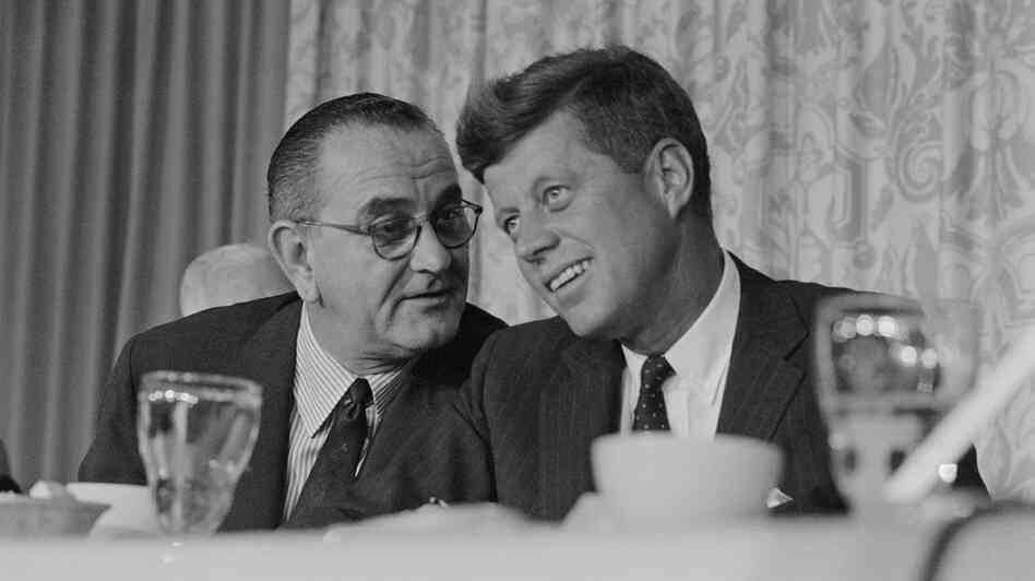 John F. Kennedy smiles as Lyndon Johnson speaks to him at breakfast during the time of the 1960 Democratic convention in Los Angeles.
