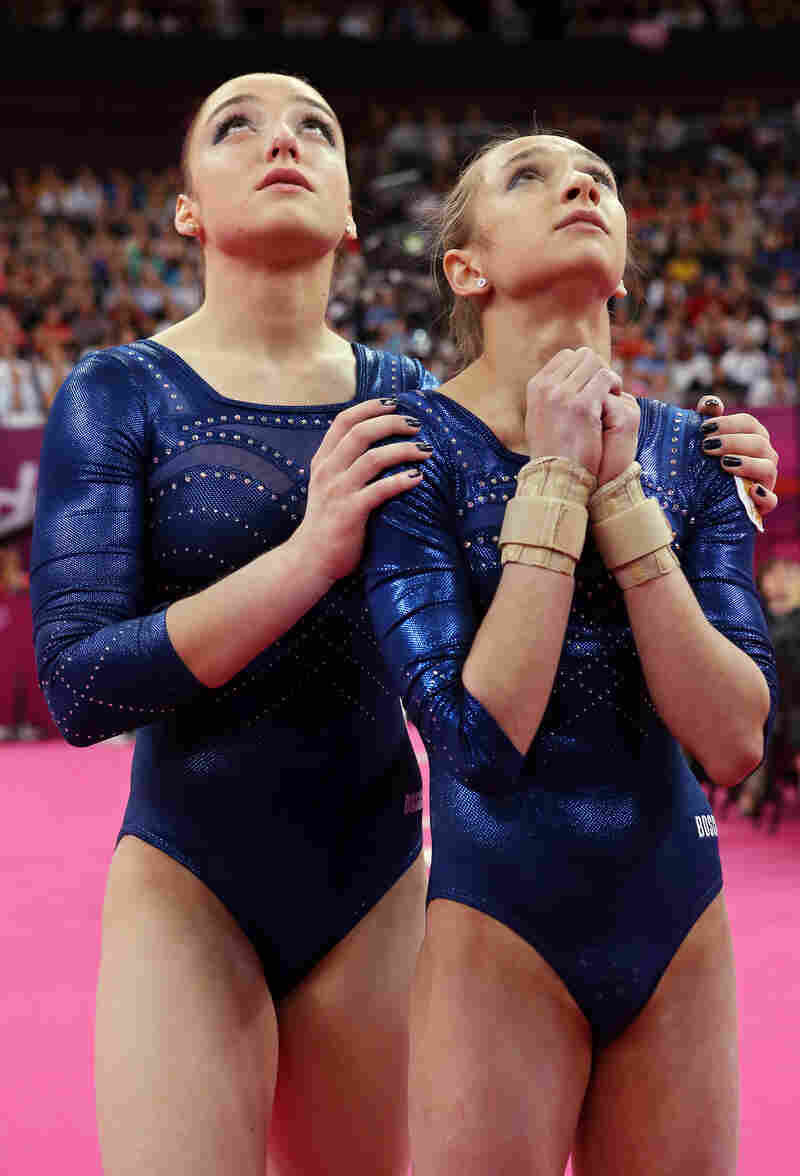 Russian gymnasts Aliya Mustafina (left) and Victoria Komova wait for the final scores to be announced in the Artistic Gymnastics Women's Individual All-Around final. Mustafina placed third and Komova placed second.