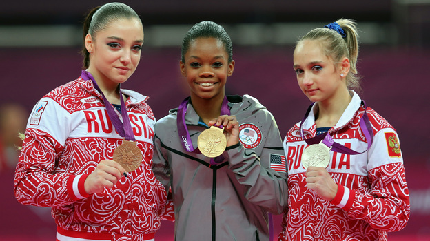 Who's The Happiest? Researchers studied photos of Olympic medalists to learn who is the happiest. Here, bronze medalist Aliya Mustafina of Russia, gold medalist Gabby Douglas of the U.S., and silver medalist Victoria Komova of Russia pose after the all-around gymnastics final. (Getty Images)