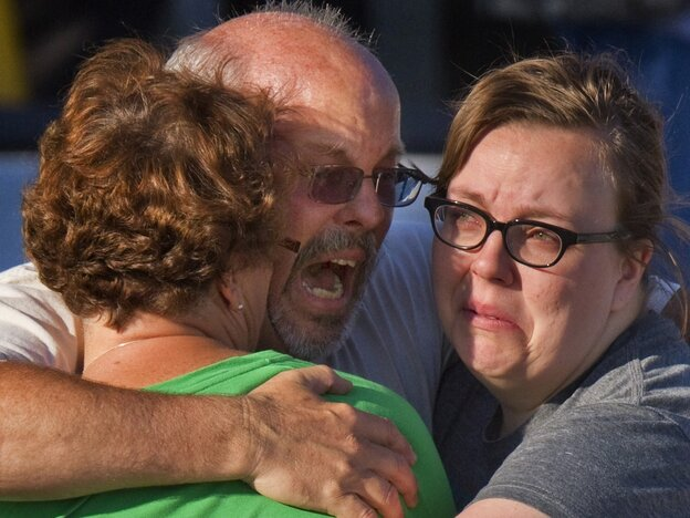 Tom Sullivan embraces family members outside Gateway High School in Aurora, Colo., on July 21. He had been searching for his son Alex,  who celebrated his 27th birthday by going to see the new Batman movie at the theater where a gunman opened fire.
