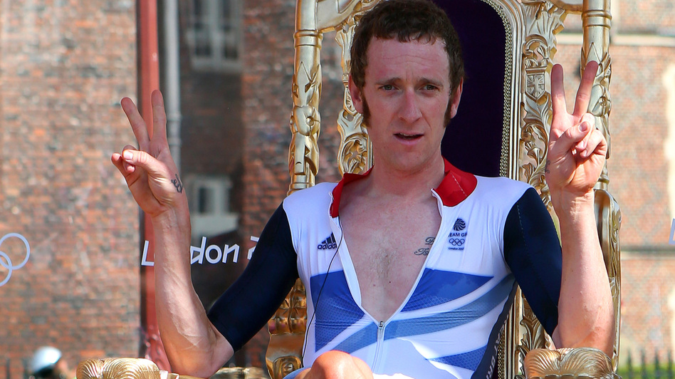 "The Mods' New King? Cyclist Bradley Wiggins sits on a chair that looks an awful lot like a throne, after winning an Olympic gold medal Wednesday. Hailed in Britain for his mod tastes and funny tweets, Wiggins celebrated his win by getting ""blind drunk,"" he said. (Getty Images)"