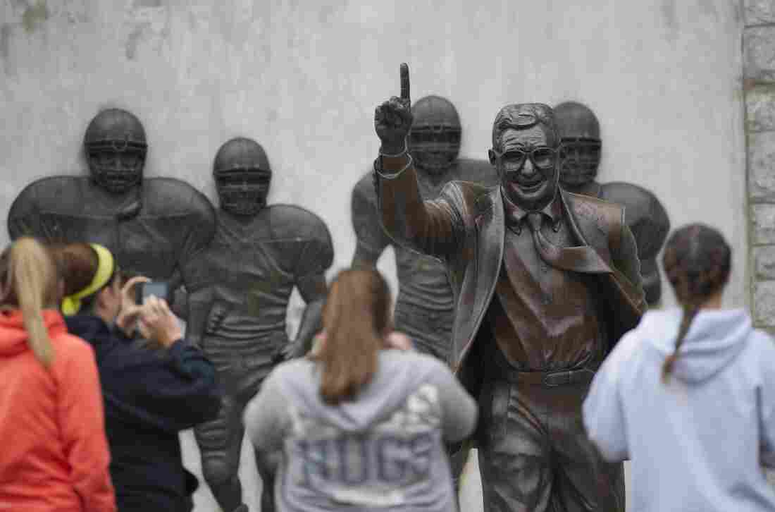 Visitors gather around the statue of former Penn State football coach Joe Paterno outside Beaver Stadium Saturday in State College, Pa.