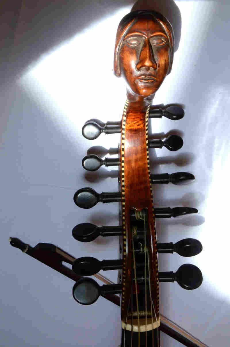 The carved head and peg box of an early 18th-century Baryton, a bass viol with additional metal strings that change the instrument's timbre.