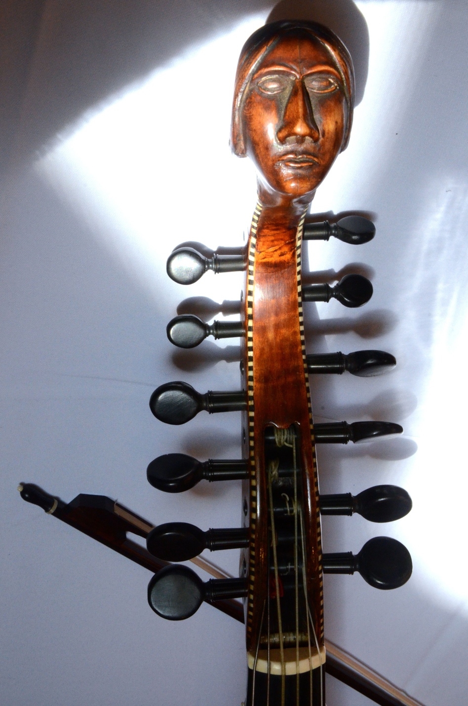 The carved head and peg box of an early 18th-century Baryton, a bass viol with additional metal strings that change the instrument's timbre.  (Scott Mason)