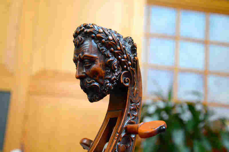A traditional carved head on an original, early 18th-century bass viol.