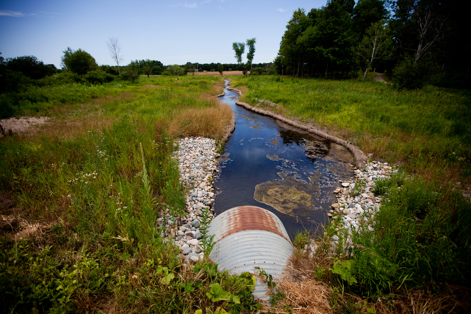 A culvert carries Talmadge Creek under a road in Marshall, Mich. After the spill, this small creek was flooded with oil, carrying it to the Kalamazoo River in the distance. Enbridge cleaned this area of oil twice. The second cleaning occurred after Bolenbaugh appeared on a local news channel falling through winter ice into a pool of oil in an area the company had declared free of oil. (NPR)