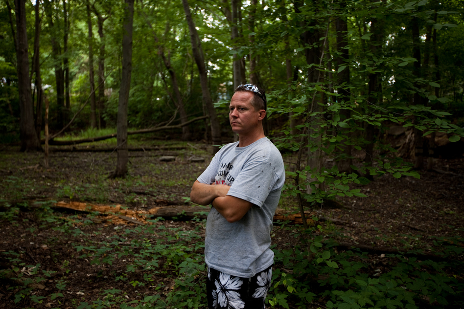 John Bolenbaugh stands in a forested stretch of the Kalamazoo River that borders a mobile home community in Battle Creek, Mich. (NPR)