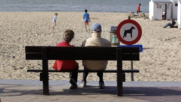 People enjoy a sunny day on the beach in Knokke, on Belgium's North Sea coast, in  April 2011. This summer, the weather hasn't been as nice — and resort owners and officials are feeling litigious over a pessimistic weather forecast. (EPA /Landov)