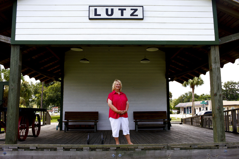 Faces of Florida's First and Main: Susan MacManus lives in her family's home on a secluded plot of land near Lutz, Fla. MacManus, shown at the old train depot across from the public library, is a political scientist and local historian. Her family was among the first to develop land around here a century ago. (NPR)