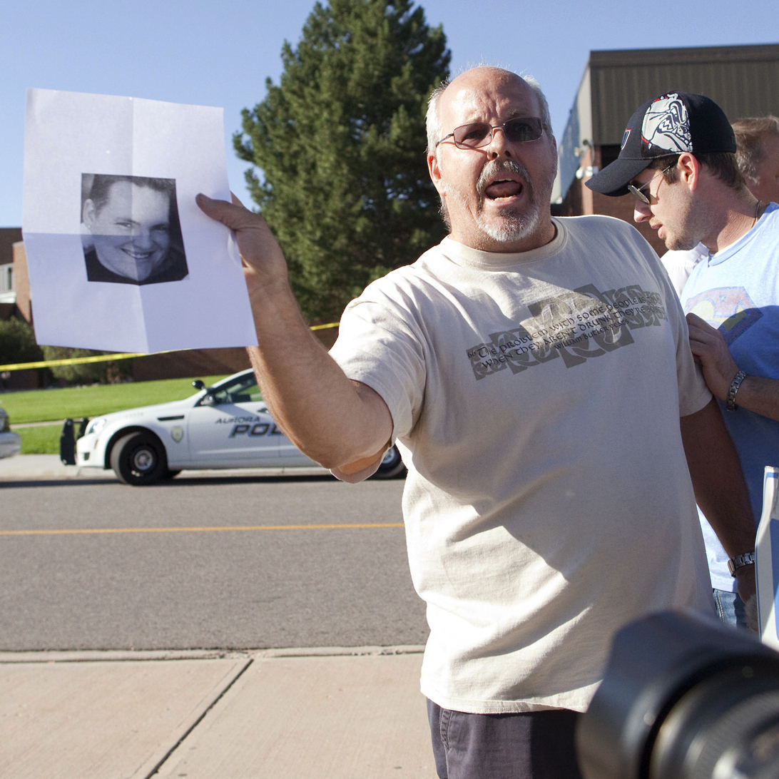 Tom Sullivan holds a picture of his son, Alex Sullivan, as he pleads with the media to help find him on July 20. Alex had gone to see a midnight showing of The Dark Knight Rises at the Aurora, Colo., theater where a shooter opened fire, killing 12 people and injuring 58 others.