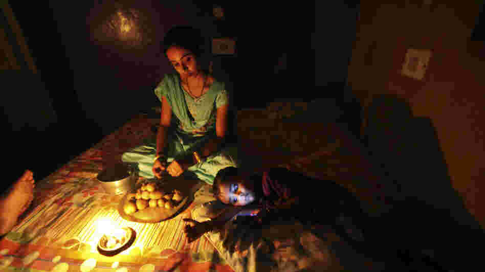 A girl prepares a meal by candlelight in Jammu, India, during the massive blackout last week.
