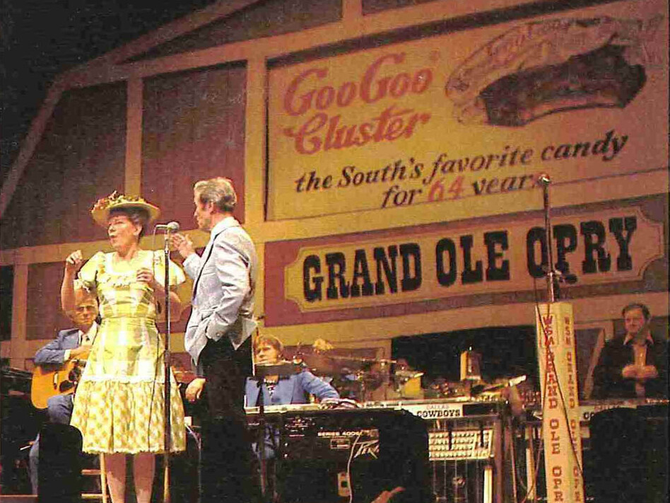 Minnie Pearl and Roy Acuff perform in front of a Goo Goo Cluster advertisement at the Grand Ole Opry, circa 1976. Coincidentally, Pearl's 100th birthday is also in October. (Courtesy of Goo Goo Cluster)