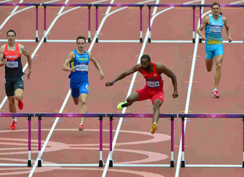 U.S. hurlders Angelo Taylor (second from right) competes in the men's 400m hurdles. He finished first in the heat. Today marks the first day of track and field events.