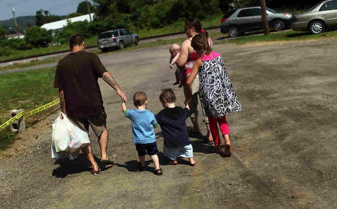 Members of the Dolan family walk home with bags of food from the Southern Tier Mobile Food Pantry in Oswego, N.Y., in June. Food banks across the nation are reporting giant spikes in demand.
