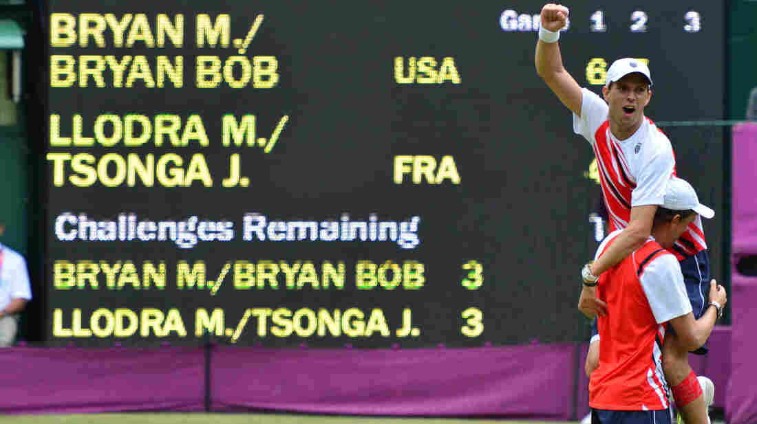 American doubles team Mike Bryan (top) and Bob Bryan celebrate after defeating France's Michael Llodra and Jo-Wilfried Tsonga in the men's doubles gold medal match of the London 2012 Olympic Games, at the All England Tennis Club.