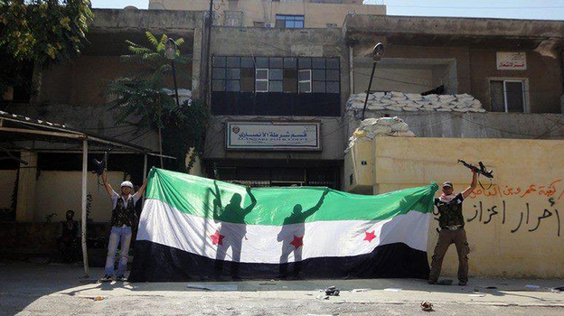 A picture released by the Syrian opposition's Shaam News Network purportedly shows Syrian rebels celebrating after taking over a police station in the Ansari district of Aleppo on Friday. (AFP/Getty Images)