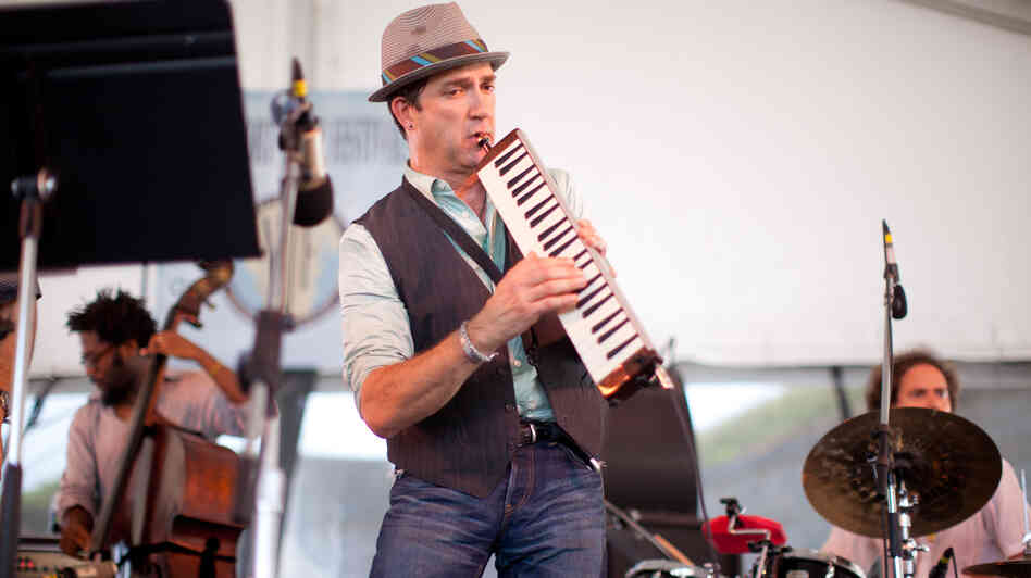 Saxophonist Peter Apfelbaum (center) plays the melodica at the 2012 Newport Jazz Festival, accompanied by Yunior Terry (left) on bass and Dafnis Prieto (right) on drums.