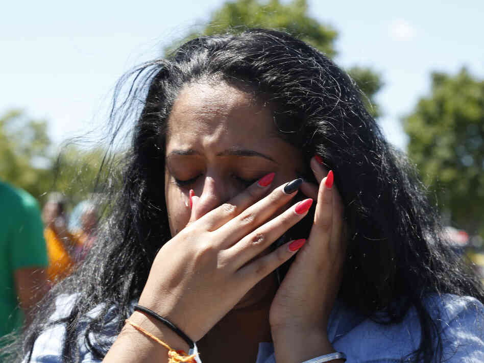 A woman waits outside the Sikh Temple of Wisconsin in Oak Creek, Wis, where a gunman opened fire and killed six people. The gunman was killed by police.