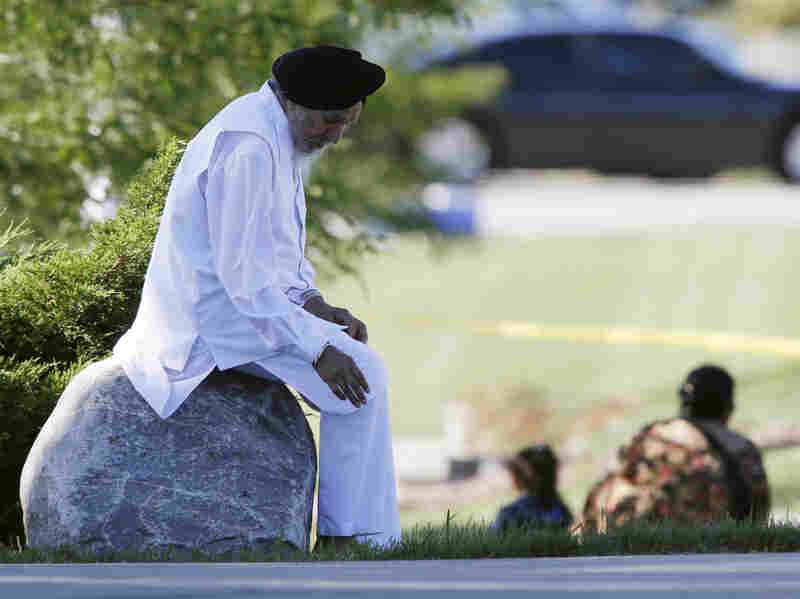 A man sits on a rock as police investigate.