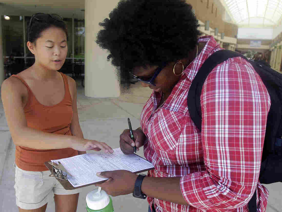 Aubrey Marks (left) helps a University of Central Florida student to register to vote in Orlando, Fla., on July 31.