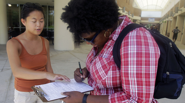 Aubrey Marks (left) helps a University of Central Florida student to register to vote in Orlando, Fla., on July 31. (AP)