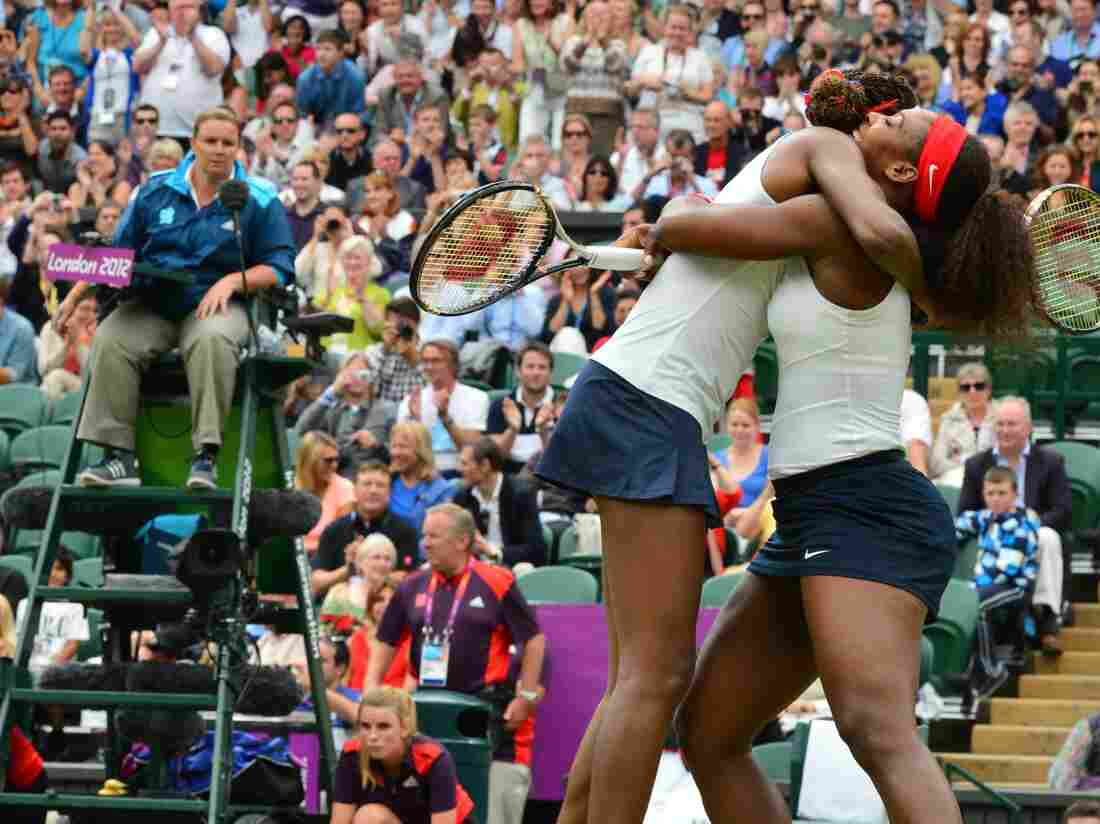 Venus (left) and Serena Williams celebrate after winning the women's doubles gold medal match today.